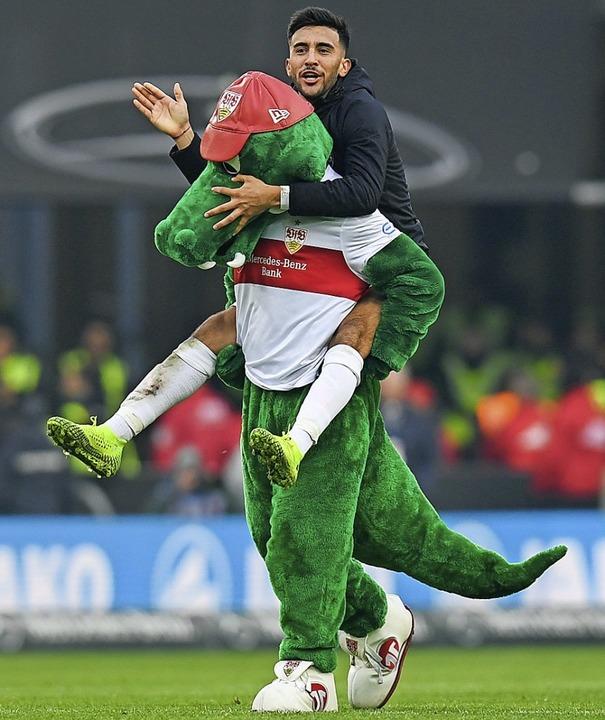 VfB-Maskottchen Fritzle freut sich mit dem Angreifer Nicolas Gonzalez.   | Foto: Tom Weller (dpa)