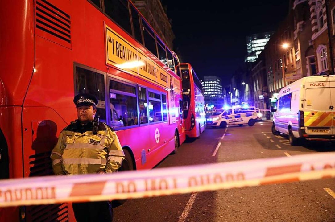 Polizeibeamte sperren den Tatort auf d... sich auf der London Bridge ereignete.  | Foto: Isabel Infantes (dpa)