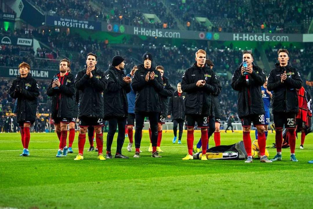 Nach dem Schlusspfiff verabschieden sich die Freiburger Spieler von ihren Fans.  | Foto: David Inderlied (dpa)