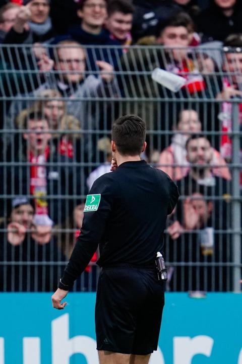 Schiedsrichter Harm Osmers steht in Sa...er Fans und wird mit Bechern beworfen.  | Foto: Uwe Anspach (dpa)