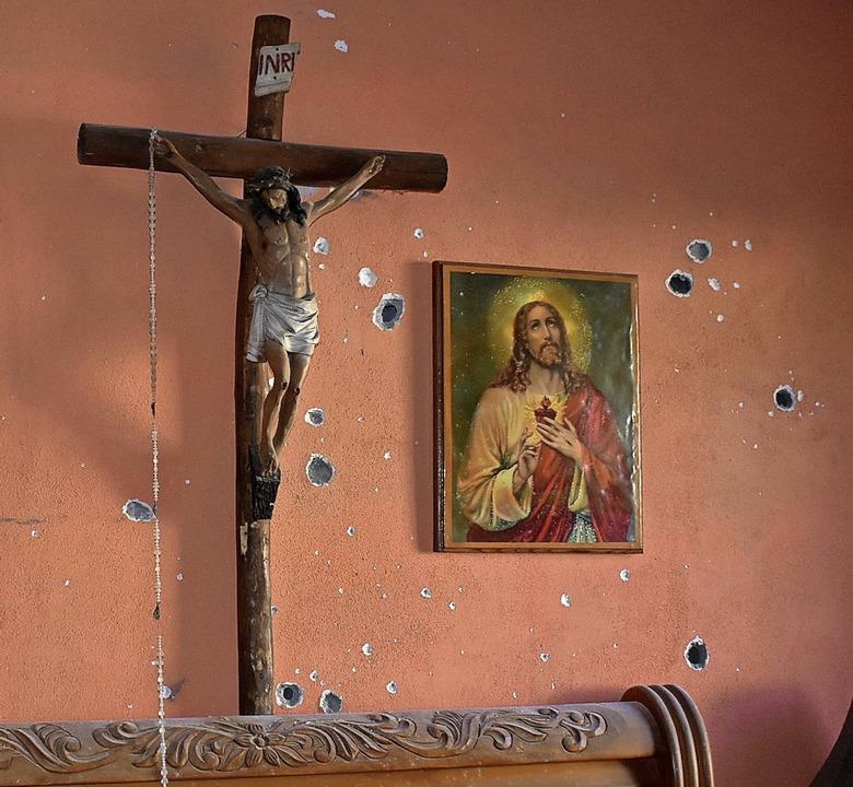 Einschusslöcher neben Kruzifix und Bildnis von Jesus Christus    Foto: Gerardo Sanchez (dpa)