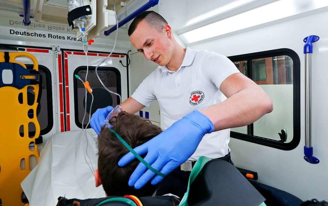 Notfallsanitäter Adrian Filser legt in... Sauerstoffmaske an (gestellte Szene).  | Foto: Thomas Warnack