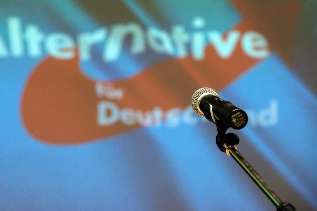 Ein Mikrofon steht beim Landesparteita...AfD auf der Bühne vor dem Partei-Logo.    Foto: Sebastian Willnow (dpa)