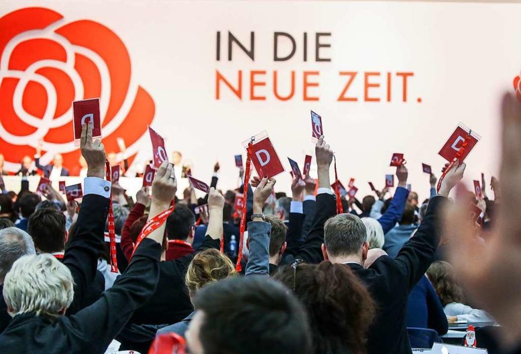 Delegierte halten beim SPD-Bundesparteitag ihre Stimmkarten hoch.  | Foto: Wolfgang Kumm (dpa)