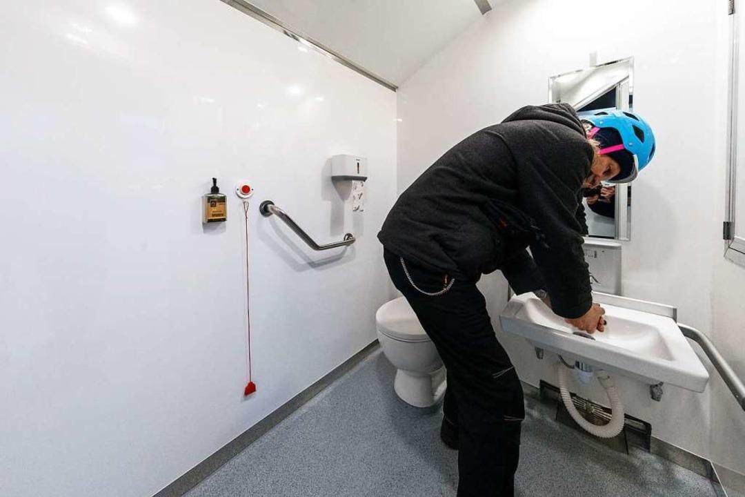 Ein Mann wäscht sich im GoBanyo-Duschbus die Hände.  | Foto: Markus Scholz (dpa)