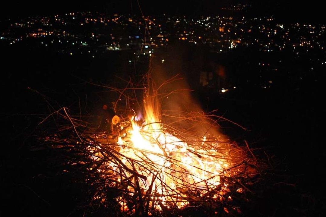 Das Mahnfeuer auf dem Tüllinger Berg vor den Lichtern von Lörrach.    Foto: Thomas Loisl Mink