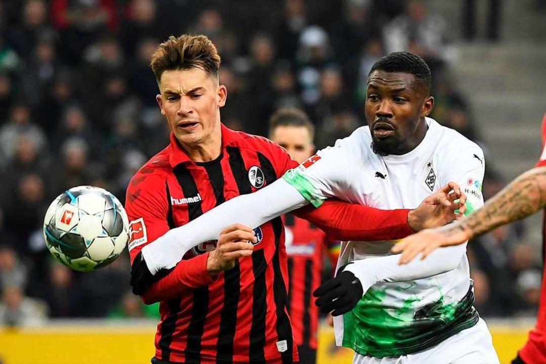 Robin Koch (links) im Zweikampf mit Marcus Thuram von Borussia Mönchengladbach  | Foto: INA FASSBENDER (AFP)