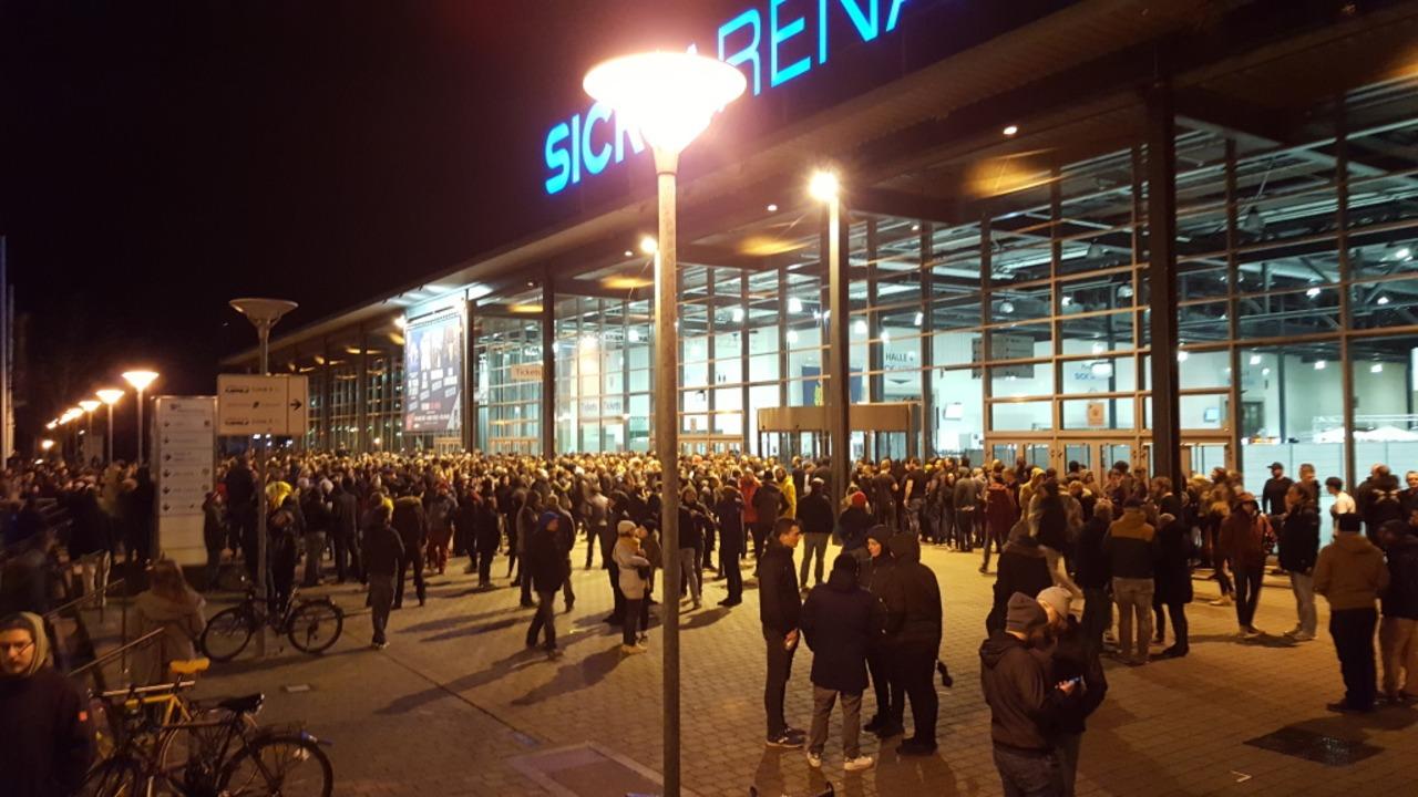 Menschen warten vor der Sick-Arena auf...pen halben Stunde war der Spuk vorbei.  | Foto: Stefan Mertlik