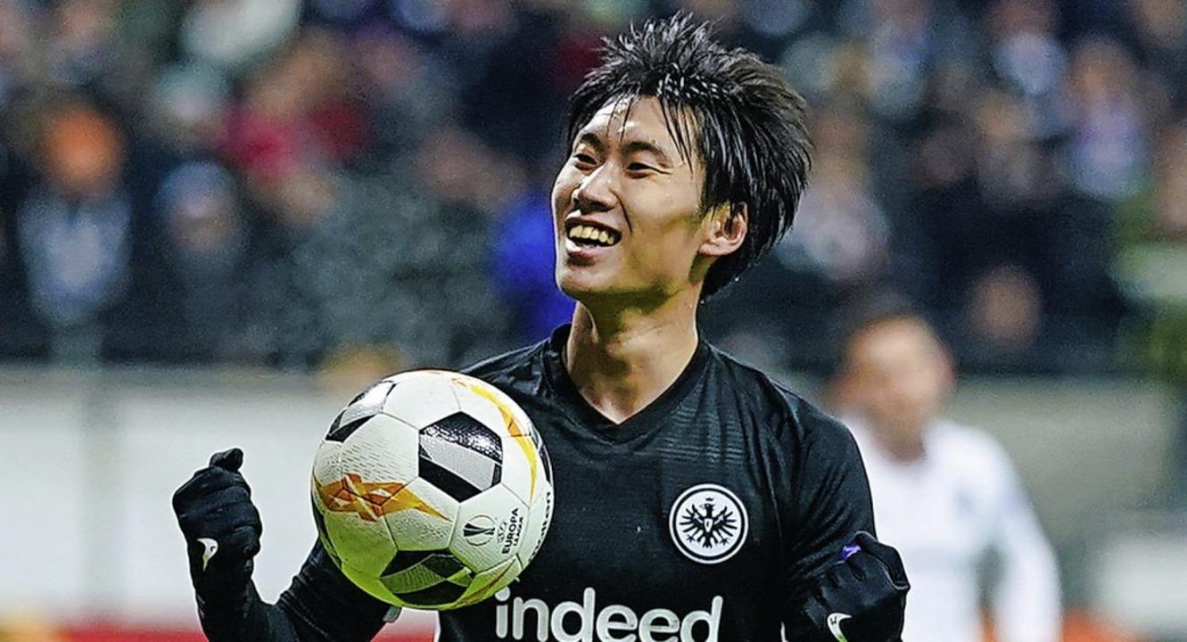 Der Frankfurter Spieler Daichi Kamada ...nen Treffer zum 2:1 – mit Ball.   | Foto: Uwe Anspach (dpa)