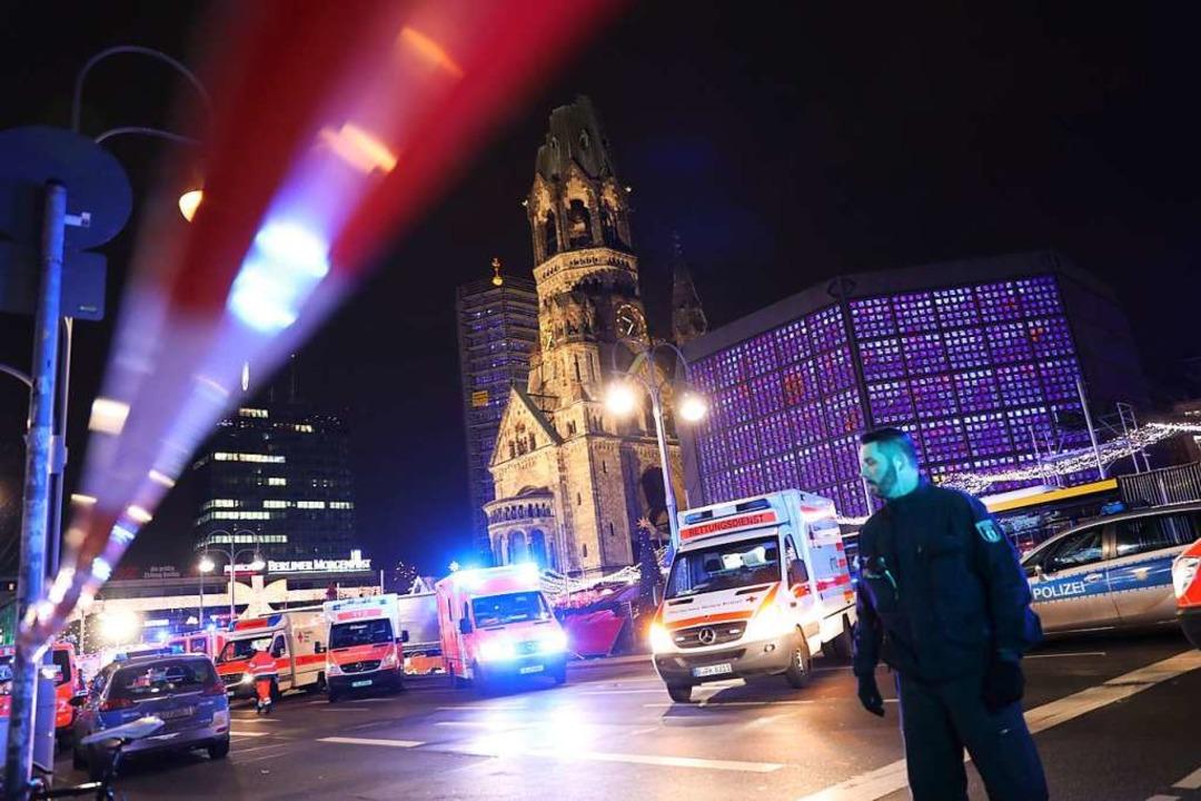 Polizisten und Rettungskräfte stehen v...m Lastwagen über den Platz gerast war.    Foto: Michael Kappeler (dpa)