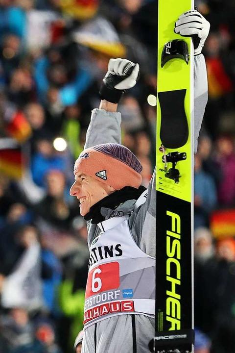 Karl Geiger freut sich über seinen zweiten Platz in Oberstdorf.  | Foto: Daniel Karmann (dpa)