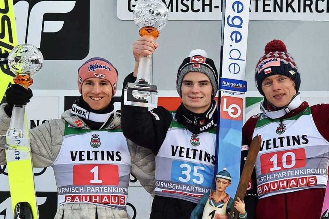 Sieger Marius Lindvik (Mitte), der Zwe... (links) und der Dritte, Dawid Kubacki  | Foto: CHRISTOF STACHE (AFP)