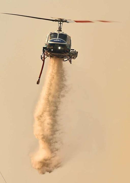 Ein Lösch-Helikopter im Einsatz.    Foto: PETER PARKS (AFP)
