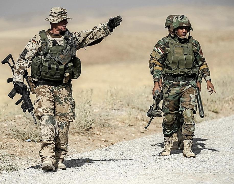 Ein Bundeswehrsoldat (links) 2016 in Erbil bei der Ausbildung irakischer Kräfte  | Foto: Michael Kappeler (dpa)