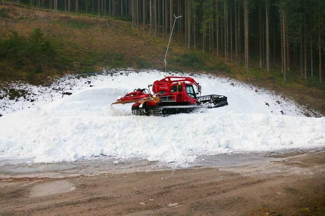 Der Pistenbully fährt den  Schnee auf dem Depot zurecht.  | Foto: Peter Stellmach