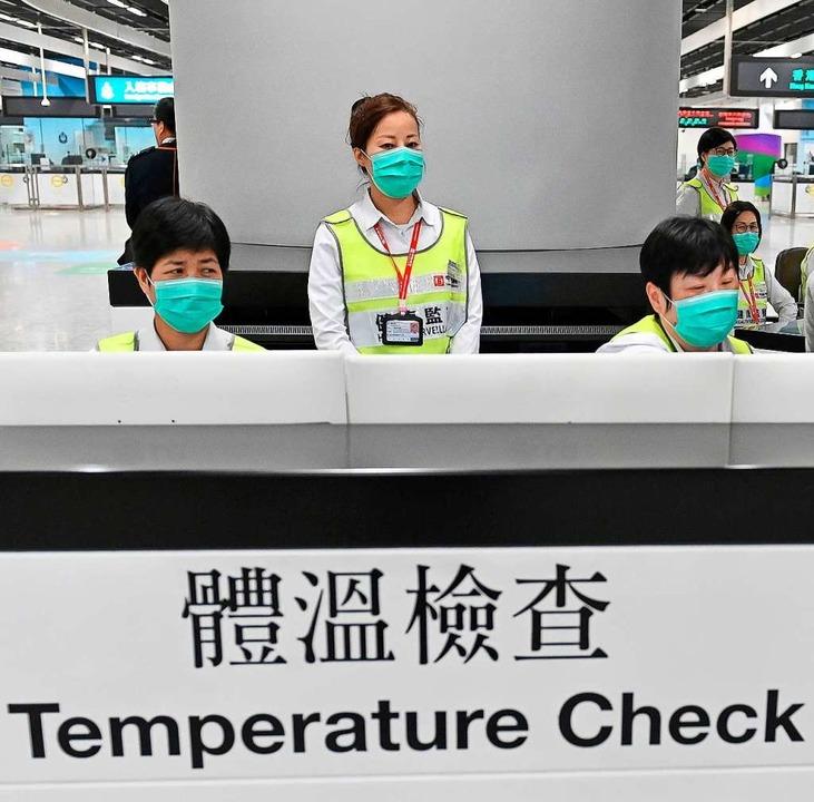 Mitarbeiter des Honkonger Gesundheitsw...ende auf ihren Gesundheitszustand hin.  | Foto: dpa