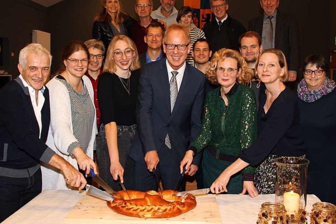 Viele Gäste halfen dabei, die Neujahrsbrezel anzuschneiden.  | Foto: Mario Schöneberg