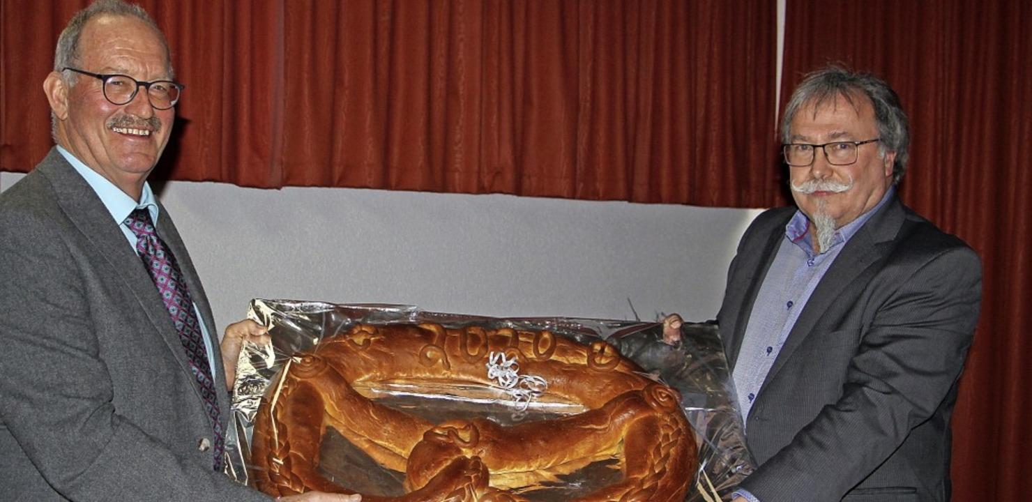 Der stellvertretende Ortsvorsteher Gis...Jost Göring eine große Neujahrsbrezel.  | Foto: Herbert Trogus