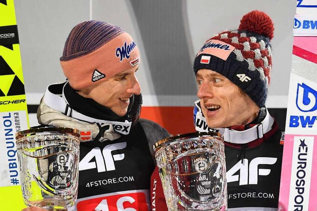 Karl Geiger (links) und Dawid Kubacki ...wie die deutschen und polnischen Fans.    Foto: CHRISTOF STACHE (AFP)