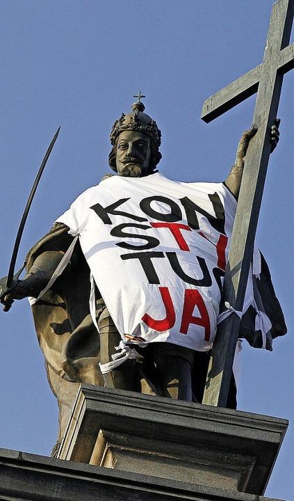 Die Statue von König Sigismund III.   ...  mit einem Protest Banner eingehüllt.  | Foto: Czarek Sokolowski (dpa)