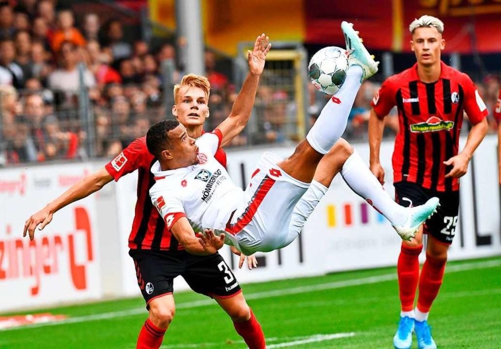 Szene aus dem Hinspiel (3:0 für den SC...ger Lienhart (l.) und Koch schauen zu.  | Foto: THOMAS KIENZLE (AFP)