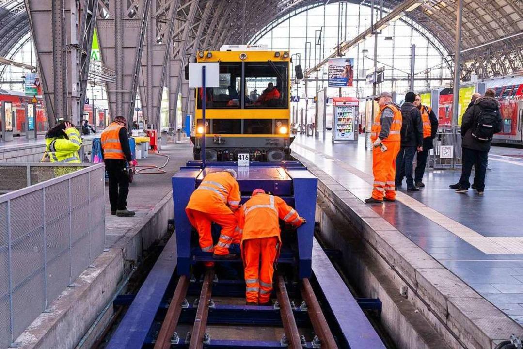 Mitarbeiter der Deutschen Bahn reparie...n beschädigten Prellbock in Frankfurt.  | Foto: Andreas Arnold (dpa)