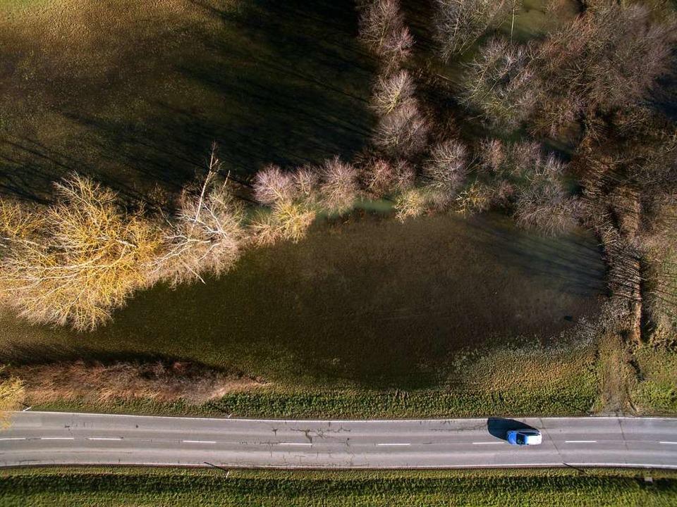 Ein Auto fährt auf der Landstraße am &... rechts im Bild ist ein Damm zu sehen.  | Foto: Marijan Murat (dpa)