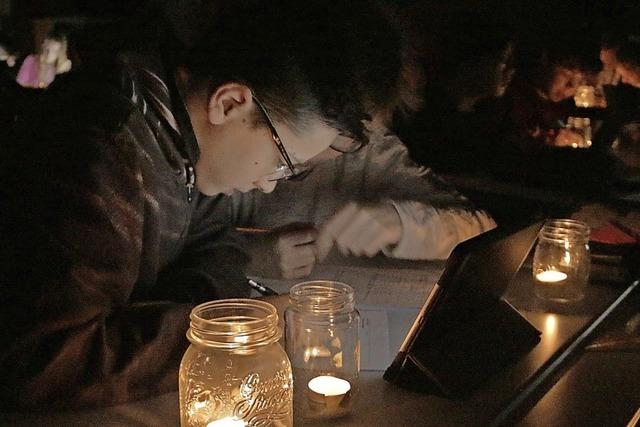 Im Kerzenschein werden Mathe-Aufgaben gelöst