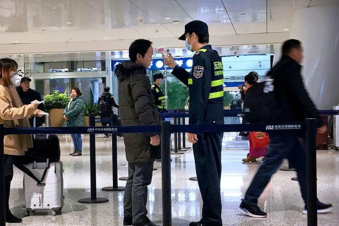 Ein Beamter misst bei einem Reisenden in Wuhan die Temperatur.  | Foto: Emily Wang (dpa)