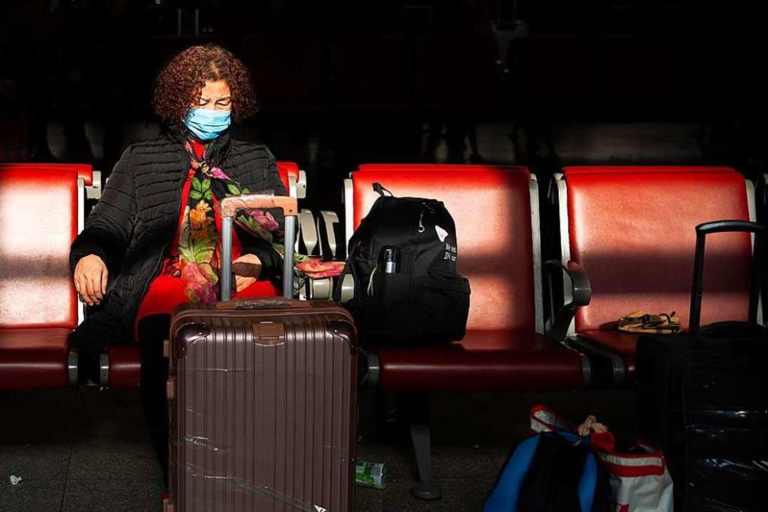 Eine Reisende am Pekinger Westbahnhof ...gegen die Verbreitung des Coronavirus.  | Foto: Mark Schiefelbein (dpa)