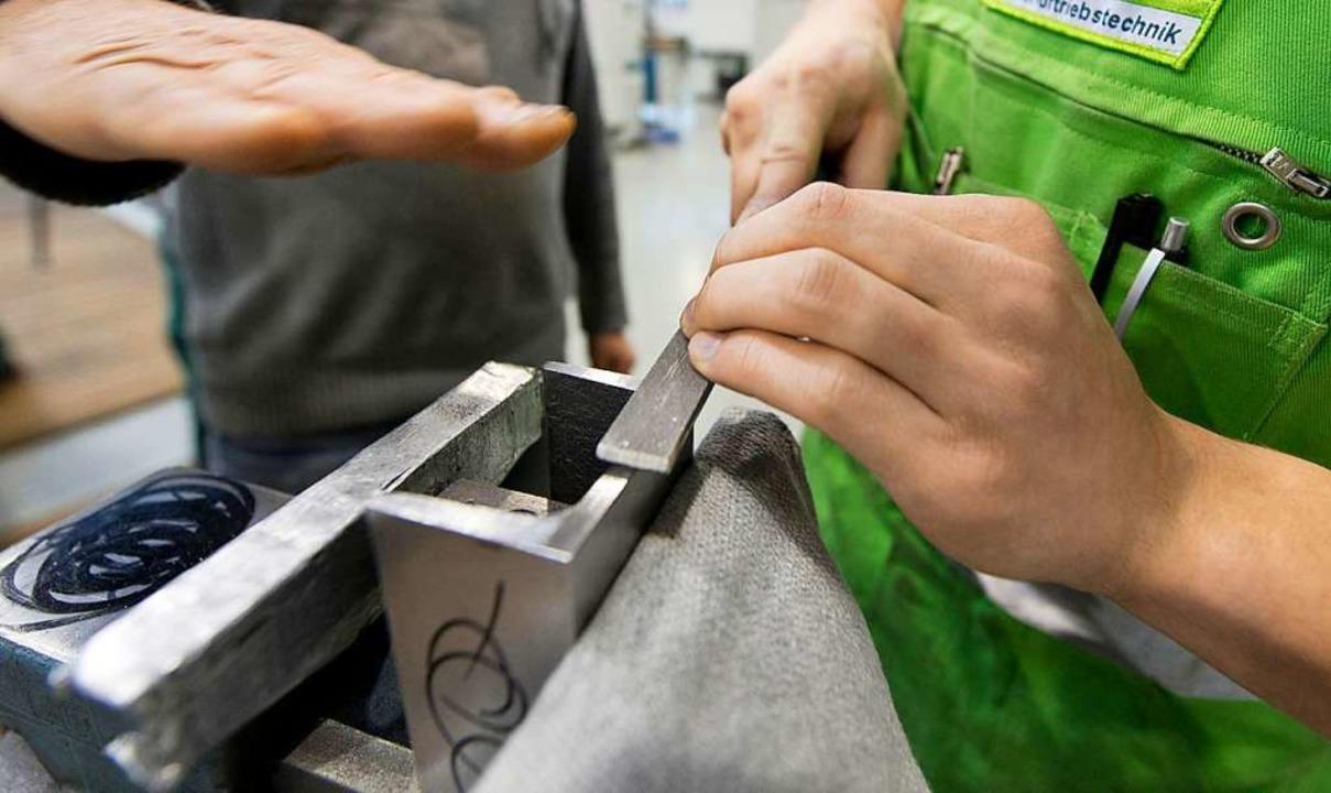 Ein Meister erklärt einem Auszubildenden das Feilen an einem Metallteil.     Foto: Patrick Seeger