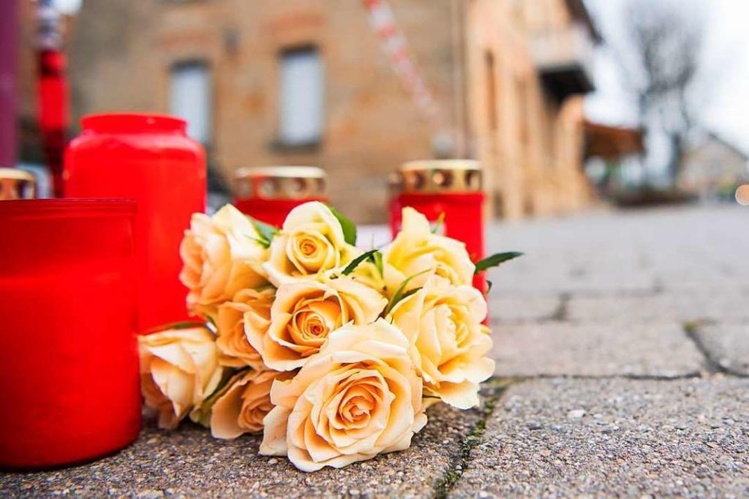 Am Tag nach den tödlichen Schüssen in ...egen Blumen und Kerzen vor dem Tatort.  | Foto: Tom Weller (dpa)
