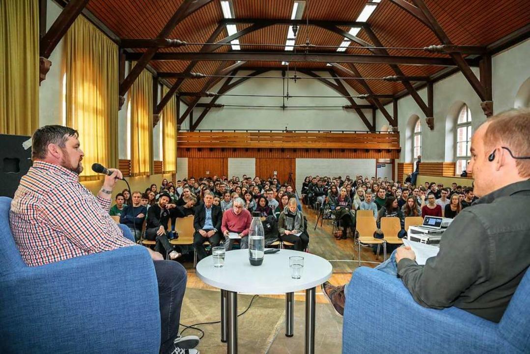 Manuel Bauer (links) im Gespräch mit G...alten Halle des Städtischen Gymnasiums  | Foto: Sandra Decoux-Kone