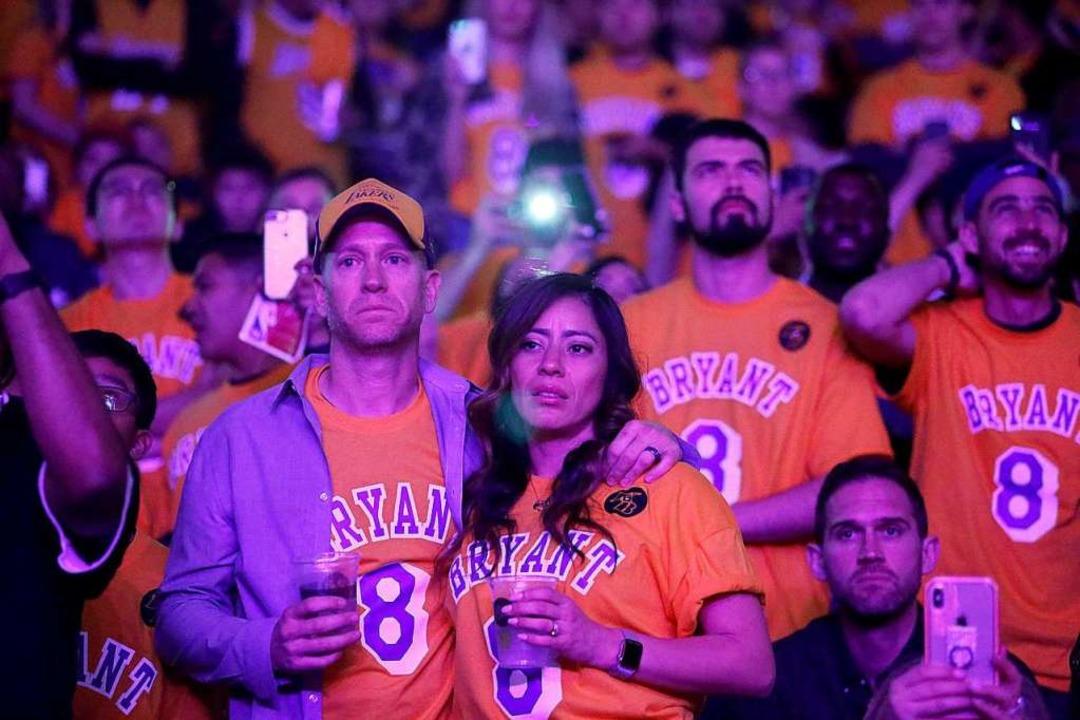 Fans trauern, während in der Halbzeit ...verstorbenen Kobe Bryant gezeigt wird.  | Foto: Ringo H.W. Chiu (dpa)