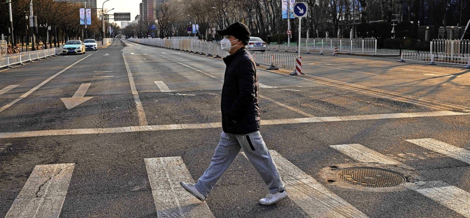 So leere Straßen gibt es in Peking sel...m Coronavirus  überquert eine Straße.   | Foto: NICOLAS ASFOURI (AFP)