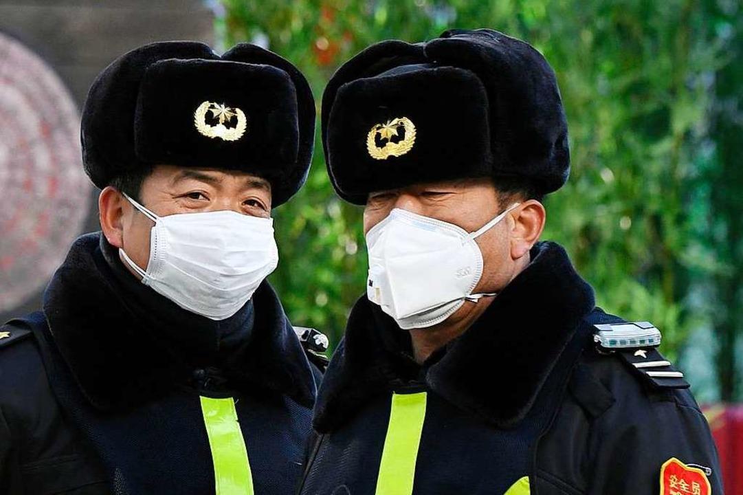 Uniformierte mit Mundschutz in Peking.  | Foto: - (dpa)