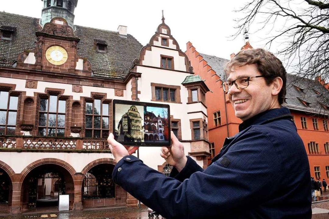 Rolf Mathis blendet zwischen historisc...ger Ansicht des Rathauses hin und her.    Foto: Thomas Kunz