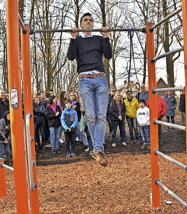 Bürgermeister Raphael Walz weiht mit Klimmzügen die Outdoor-Anlage ein.   | Foto: Andrea Steinhart