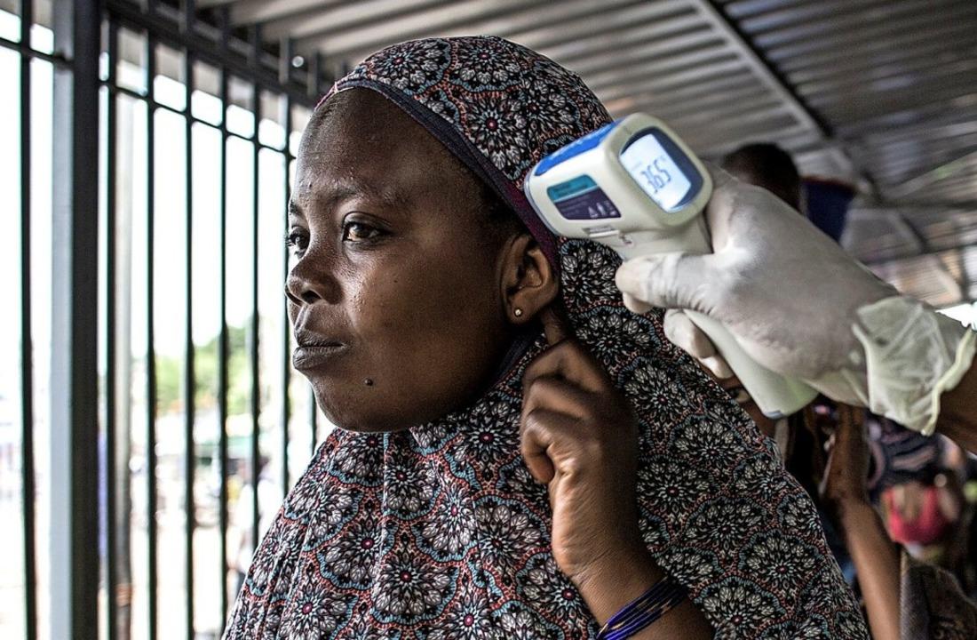 In einer Ebola-Screening-Station im Ko...Körpertemperatur einer Frau gemessen.   | Foto: JOHN WESSELS (AFP)
