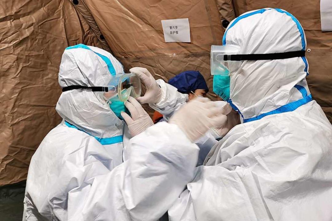 Zwei Ärzte richten sich im Krankenhaus von Wuhan ihre Schutzkleidung.    Foto: Gao Xiang (dpa)