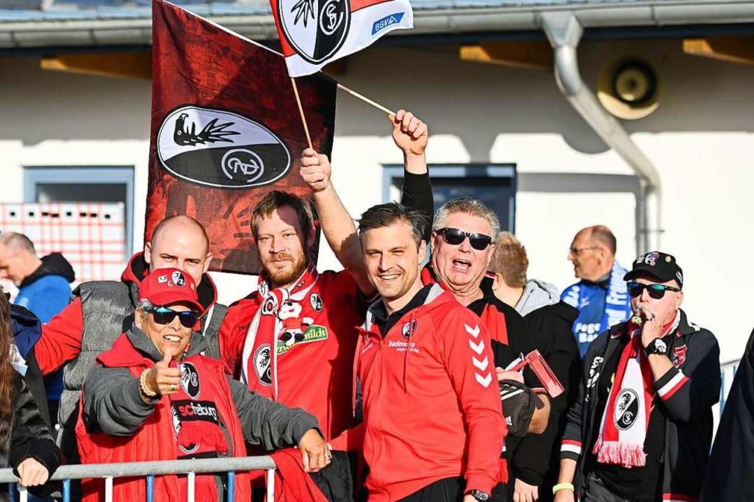 Fans feiern mit dem Trainer den Auswärtssieg.  | Foto: Achim Keller