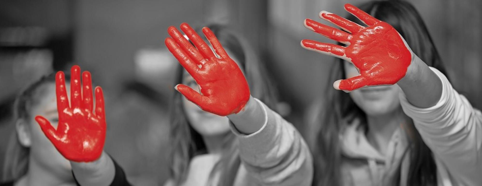 Mit der roten Hand als Symbol protesti...Auseinandersetzungen auf dieser Welt.     Foto: Thomas Steuber