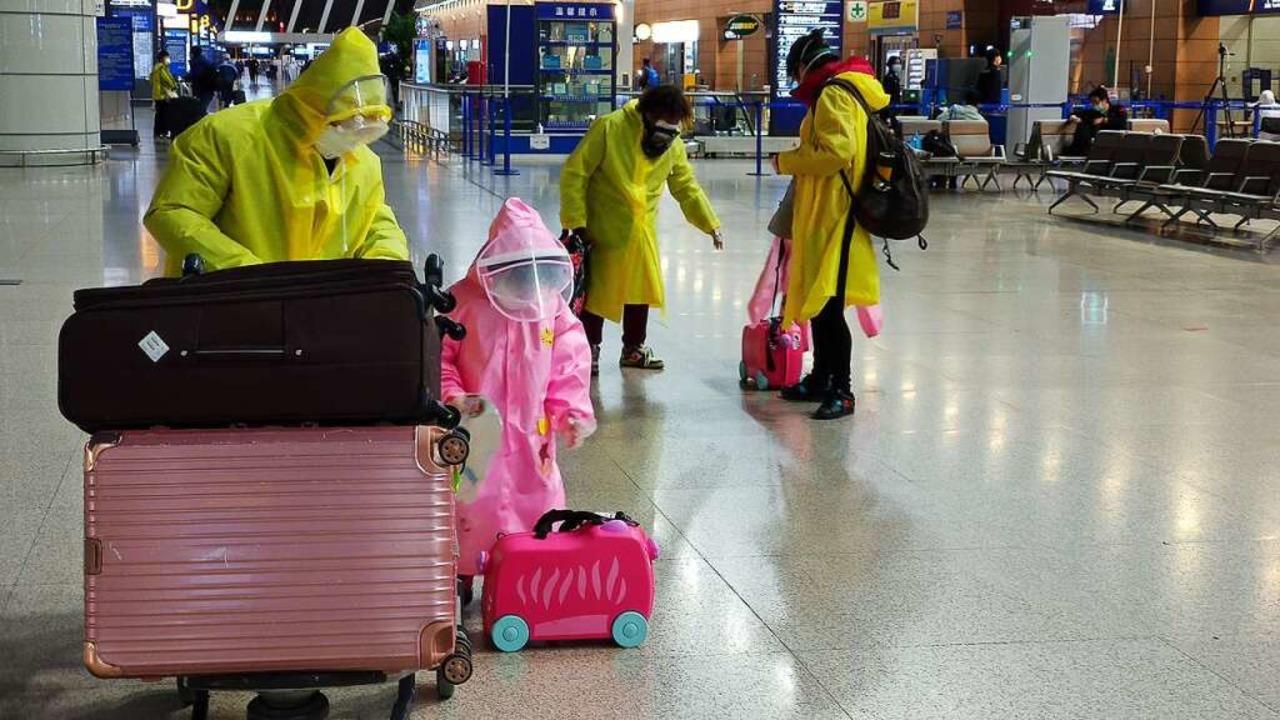 Menschen in Schutz-Regencapes und mit Mundschutz am Flughafen in Schanghai    Foto: Klaus Gabriel