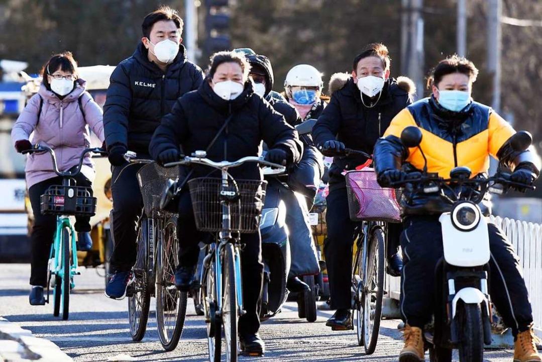 In Peking fahren Menschen mit Atemmask...aus Sicherheitsgründen in Deutschland.  | Foto: - (dpa)