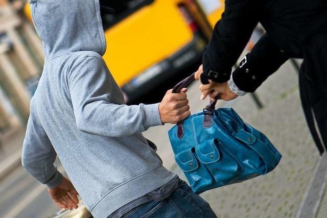 Mann klaut Geldbeutel aus Handtasche einer Frau
