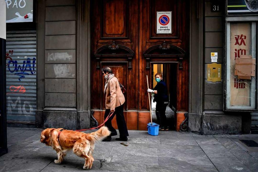 Italien, Mailand: Eine Frau mit Mundsc...ährend eine Frau mit Hund vorbeiläuft.  | Foto: Claudio Furlan (dpa)