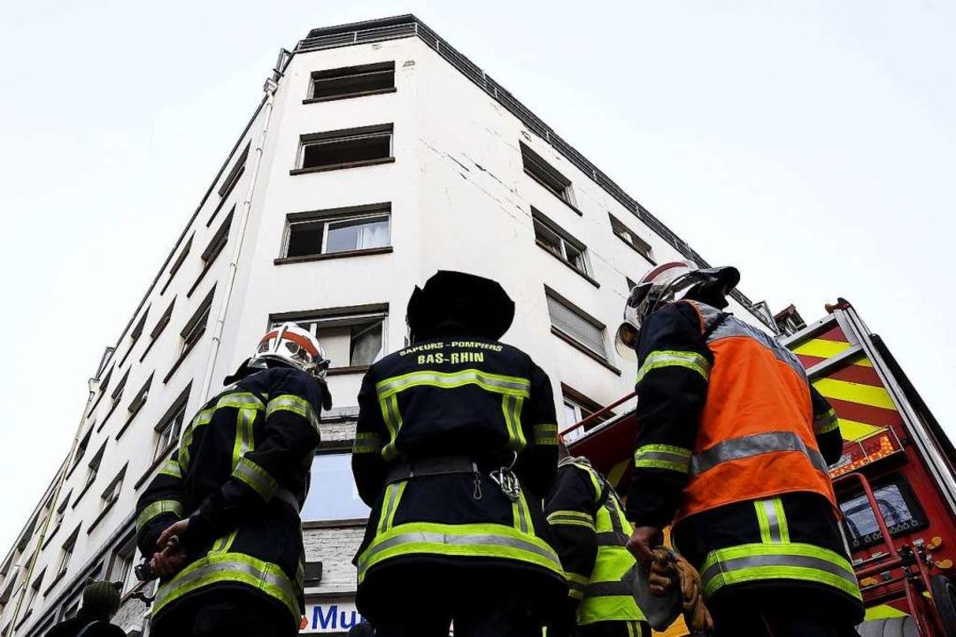 Feuerwehrleute an dem Wohnhaus im Stra...lage könnte den Brand ausgelöst haben.  | Foto: PATRICK HERTZOG (AFP)