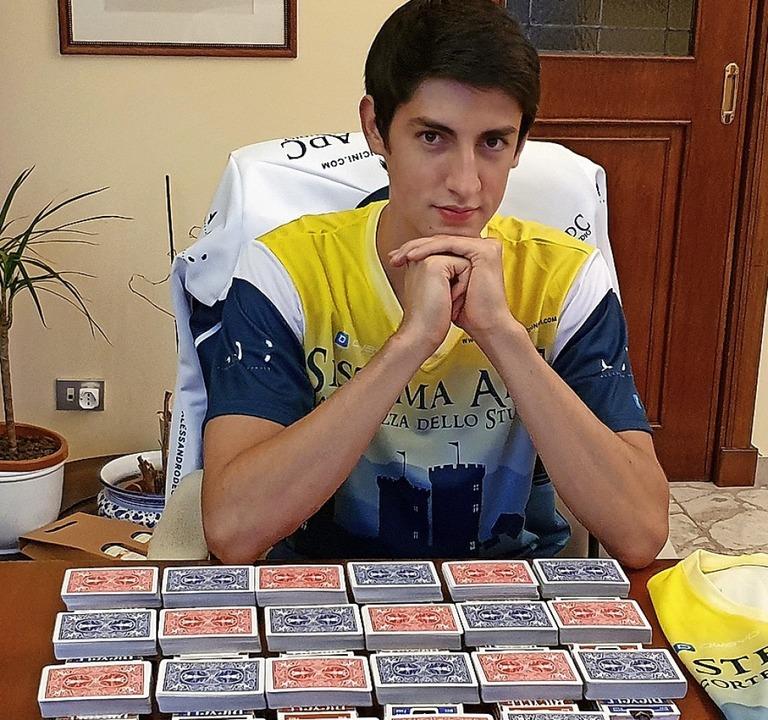 Andrea Muzii sitzt vor Kartensätzen, die er auswendig lernt.   | Foto: Alvise Armellini