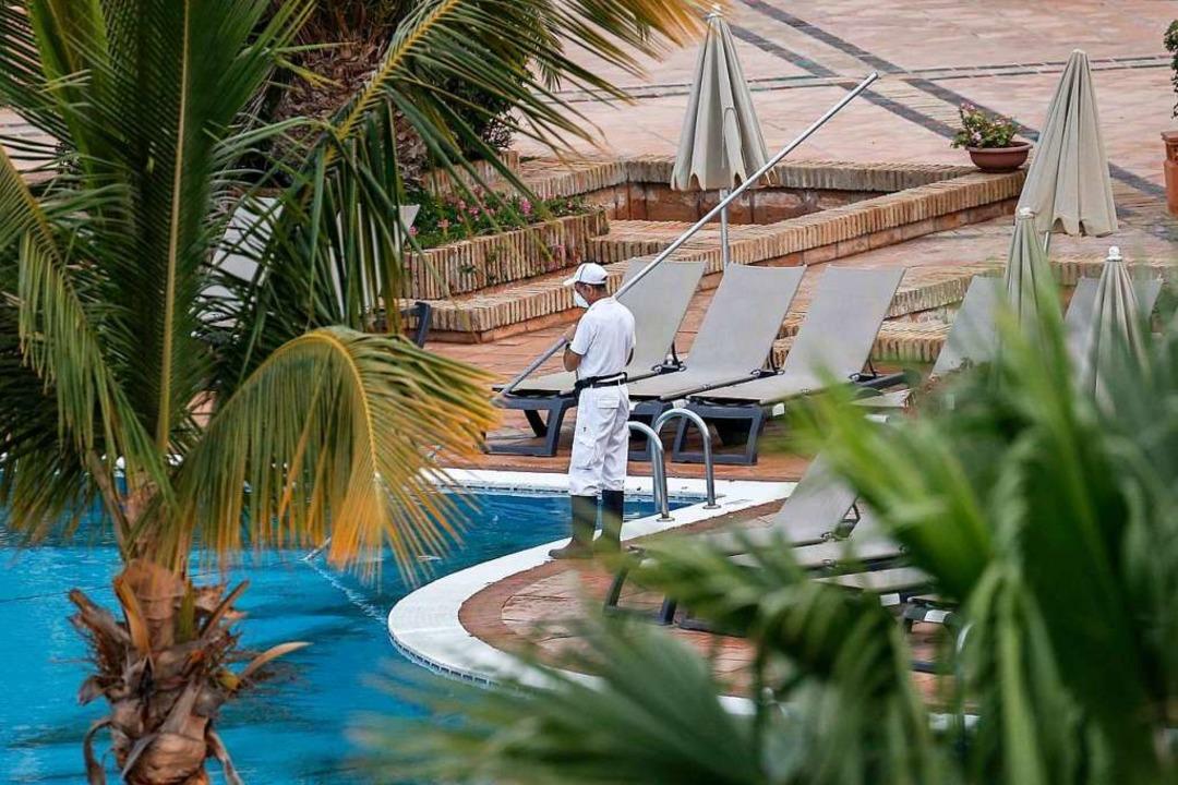 Ein Mitarbeiter reinigt den Pool des H...iterhin durch die Polizei abgeriegelt.  | Foto: Joan Mateu (dpa)