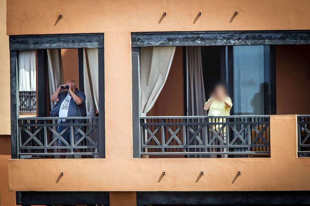 Hotelgäste stehen auf den Balkonen des Hotels.  | Foto: Arturo Rodríguez (dpa)